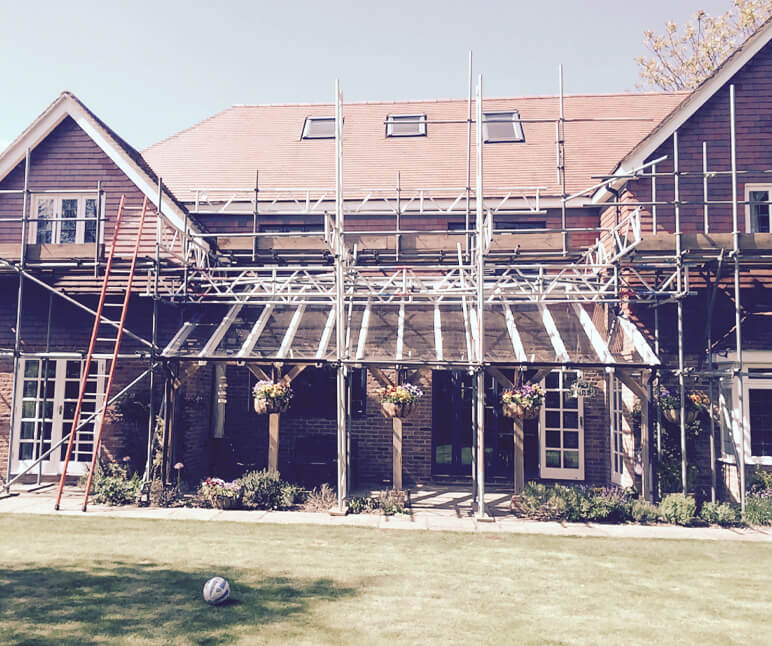 Exterior of property with scaffolding and ladders